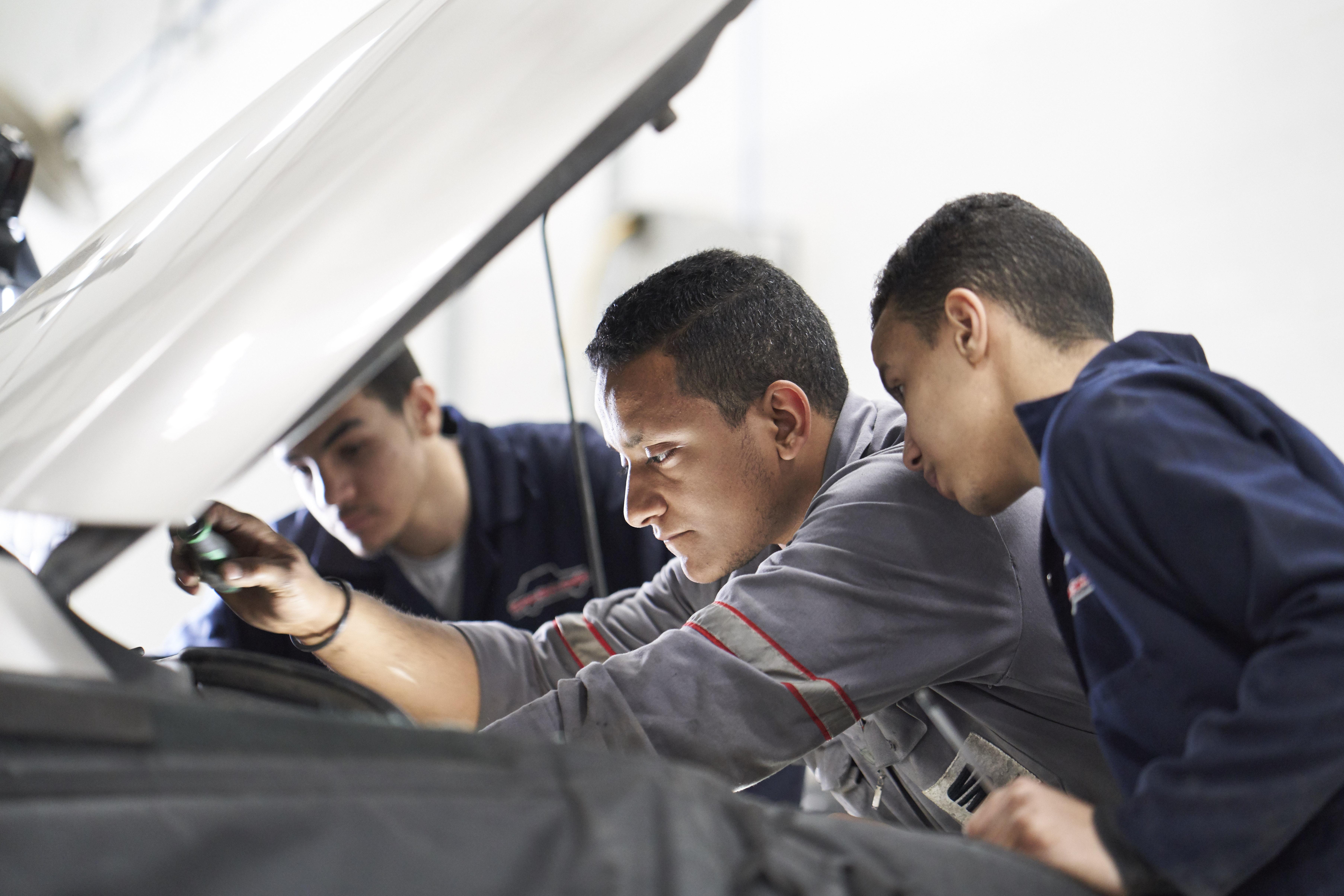 PAMA: Mechaniker schauen unter eine Motorhaube