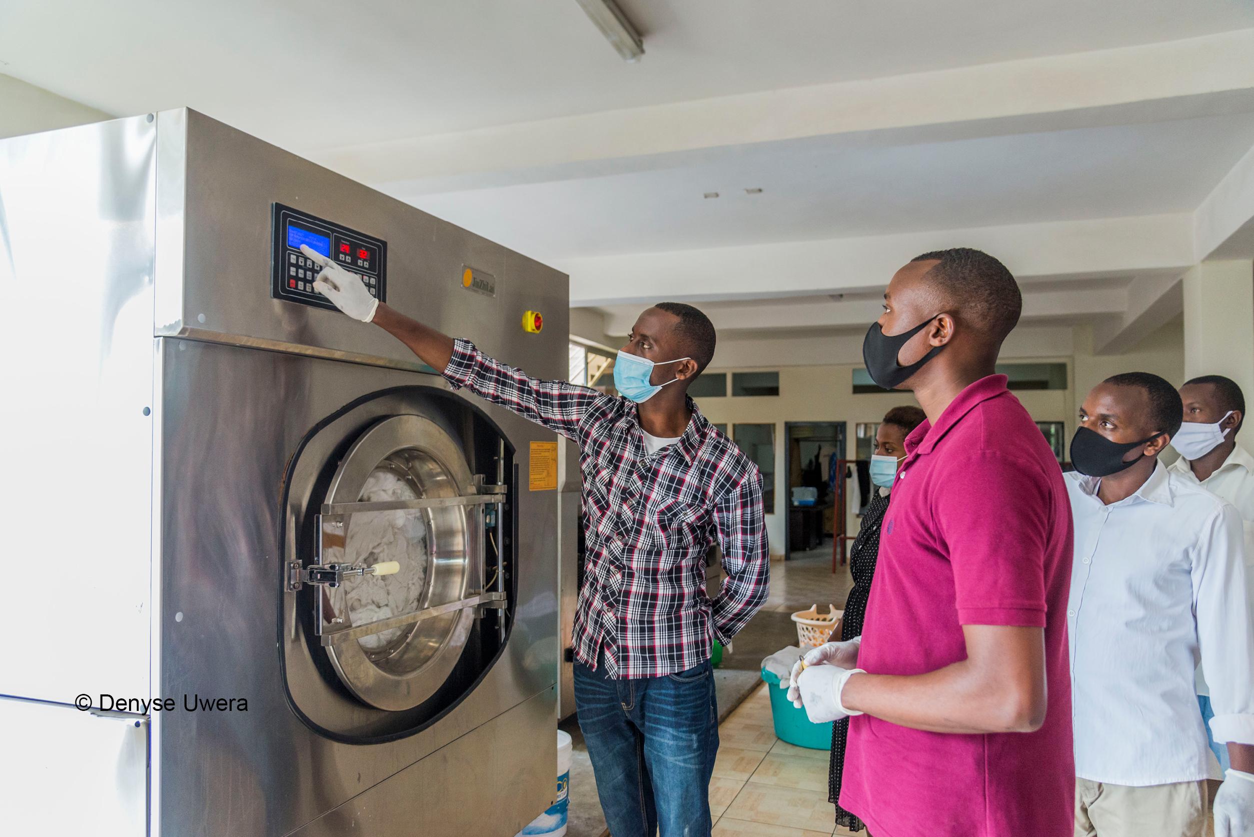 Mann zeigt Kollegen eine Waschmaschine