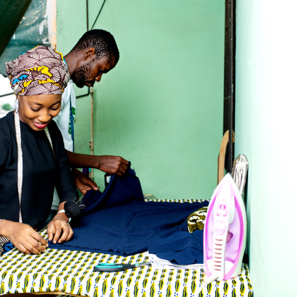 Man and woman sew on garment