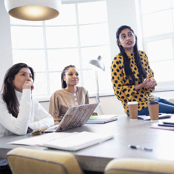 Attentive businesswomen listening in conference room meeting