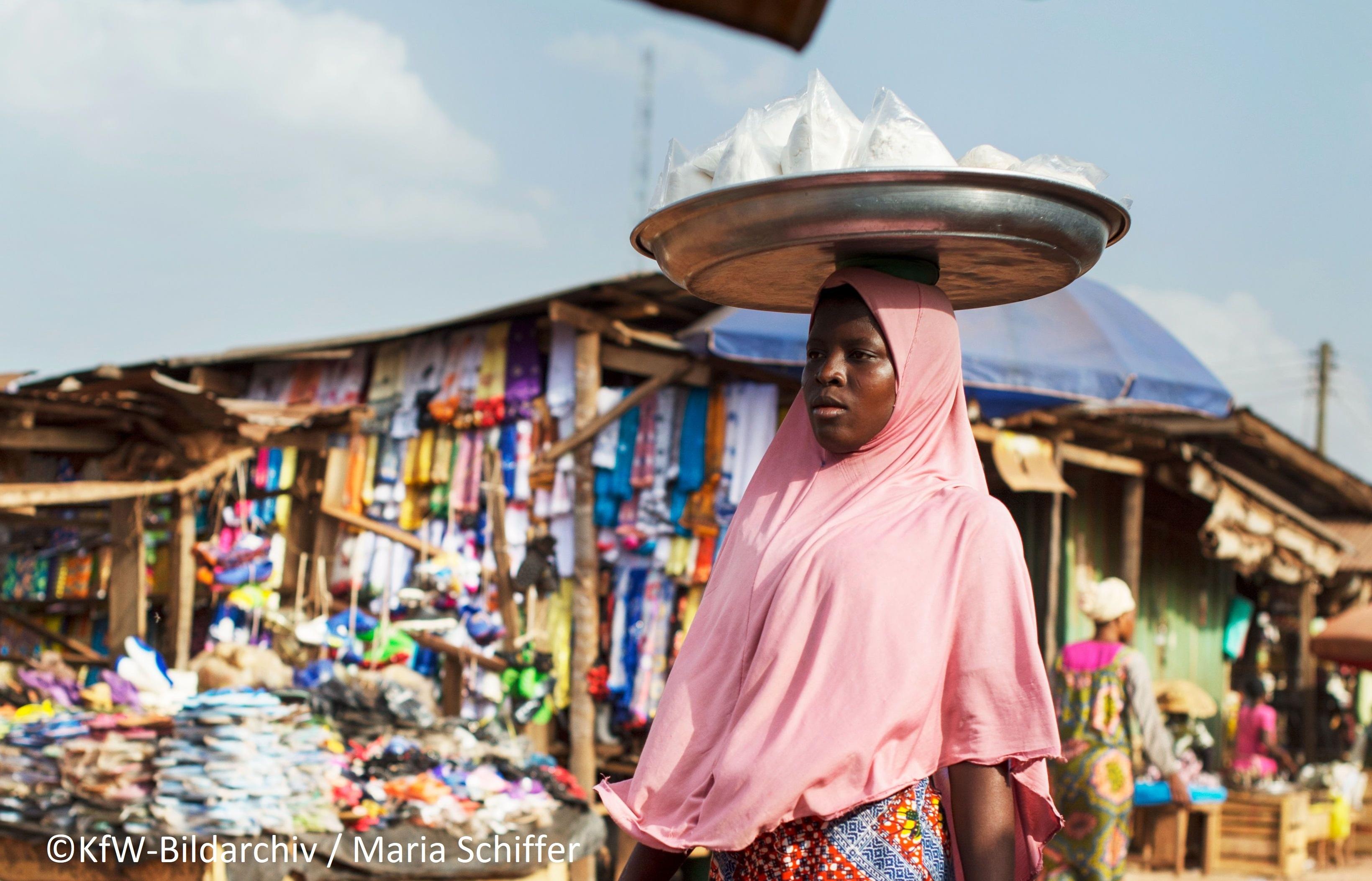 Ghanaische Frau trägt Lebensmittel in einer Schale auf dem Kopf